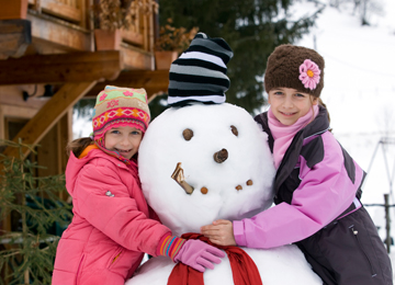 2 girls hugging snowman