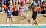 Children jumping into outdoor pool