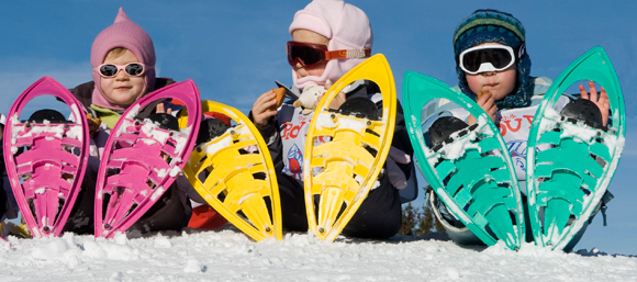 Children wearing coloured snowshoes