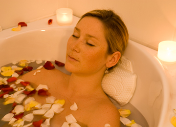 Lady relaxing in bath with petals